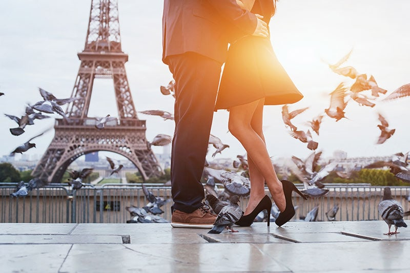 A Man And Woman Embrace In Front Of The Eiffel Tower On Their Honeymoon Booked By A Luxury Travel Planner